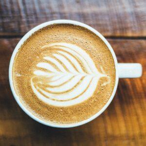 Coffee with leaf design on wood