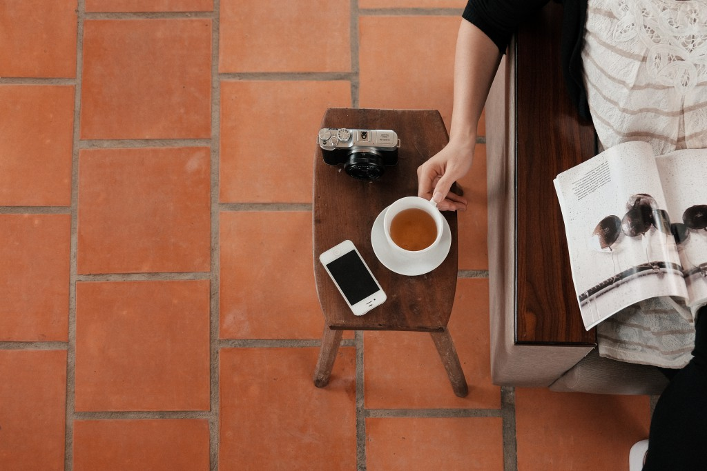 woman drinking coffee while using smartphone