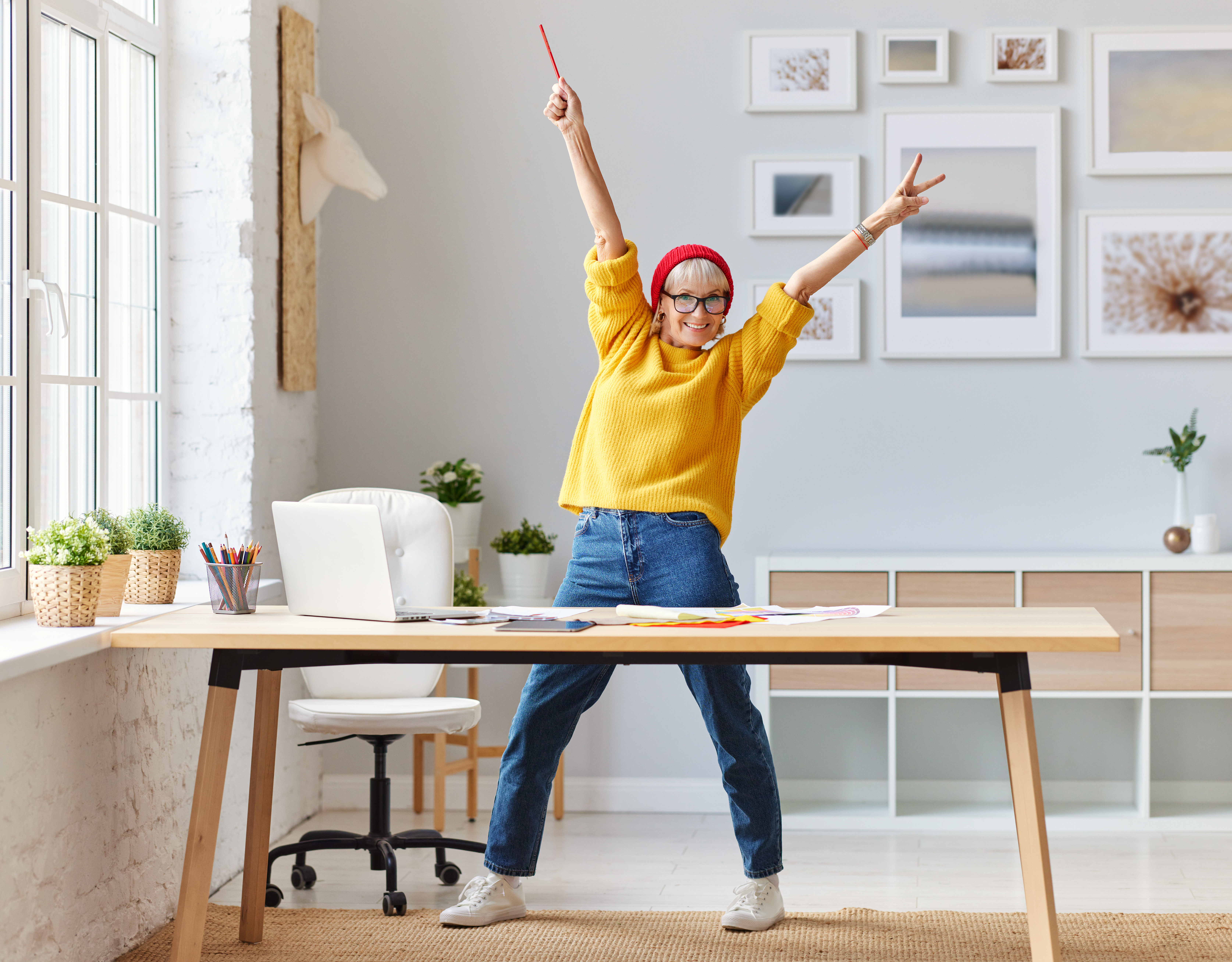 cheerful elderly woman freelancer creative designer in a red hat having fun and dancing in workplace.